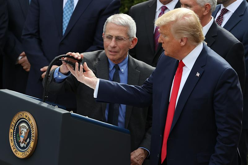 President Trump adjusts the microphone for National Institute Of Allergy And Infectious Diseases director Anthony Fauci during a news conference. (Chip Somodevilla/Getty Images)