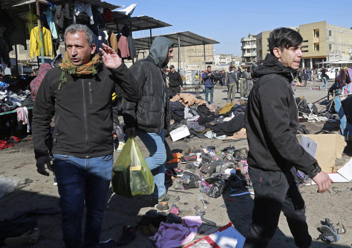 People and security forces gather at the site of a deadly bomb attack in Baghdad, Iraq, Thursday, Jan. 21, 2021. Iraq's military said twin suicide bombings at the Bab al-Sharqi commercial area in central Baghdad Thursday ripped through the busy market killing over two dozen and wounding over 70, with some in serious condition. (AP Photo/Hadi Mizban)