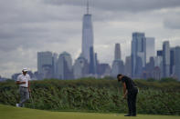 Patrick Cantlay, right, putts as Collin Morikawa, left, watches on the 14th green in the first round of play at the Northern Trust golf tournament, Thursday, Aug. 19, 2021, at Liberty National Golf Course in Jersey City, N.J. (AP Photo/John Minchillo)