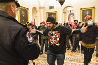 Supporters of President Donald Trump are confronted by Capitol Police officers outside the Senate Chamber at the Capitol, Wednesday, Jan. 6, 2021 in Washington. (AP Photo/Manuel Balce Ceneta)