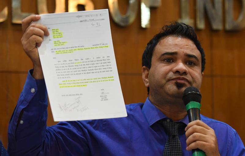 Dr. Kafeel Khan shows a document absolving him of medical negligence and corruptionduring a press conference in New Delhi on 28 September, 2019. (Photo: Hindustan Times via Getty Images)