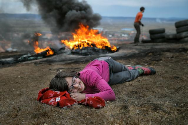 In this photo taken on Sunday, March 10, 2019, a little girl laughs during a ritual marking the upcoming Clean Monday, the beginning of the Great Lent, 40 days ahead of Orthodox Easter, on the hills surrounding the village of Poplaca, in central Romania's Transylvania region. Romanian villagers burn piles of used tires then spin them in the Transylvanian hills in a ritual they believe will ward off evil spirits as they begin a period of 40 days of abstention, when Orthodox Christians cut out meat, fish, eggs, and dairy. (AP Photo/Vadim Ghirda)