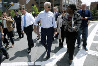 Former vice president and Democratic presidential candidate Joe Biden speaks with a woman as he walks with Boston Mayor Marty Walsh, left, on Wednesday, June 5, 2019, in downtown Boston. (AP Photo/Steven Senne)