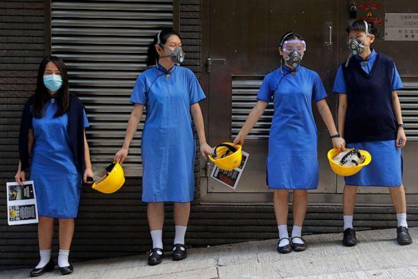 PHOTO: Students wearing masks hold hands while holding yellow helmets, a symbol of the pro-democracy protests, outside St. Stephen's Girls' College in Hong Kong, Sept. 9, 2019. (Kin Cheung/AP)