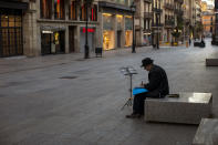 FILE - In this Sunday, March 15, 2020 file photo, a man sits, in an empty street in Barcelona, Spain. The European Union on Tuesday, April 21, 2020 says its vaunted tourism industry is facing decline due to the coronavirus crisis while Internal market Commissioner Thierry Breton says it should be the prime sector to receive over a fifth of all recovery funds. (AP Photo/Emilio Morenatti, File)