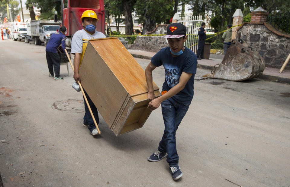<p>Neighbors carry a wooden cabinet from a building damaged by the 7.1-magnitude earthquake in San Gregorio Atlapulco, Mexico, Friday, Sept. 22, 2017. Mexican officials are promising to keep up the search for survivors as rescue operations stretch into a fourth day following Tuesday's major earthquake that devastated Mexico City and nearby states. (AP Photo/Moises Castillo) </p>