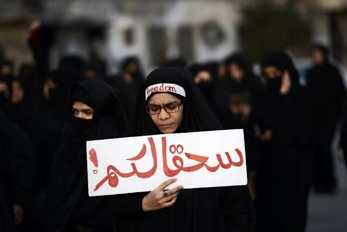 """A Bahraini woman takes part in a protest in the village of Jidhafs, west of Manama, against the execution of prominent Shiite Muslim cleric Nimr al-Nimr by Saudi authorities, on January 2, 2016. The writing in Arabic reads """"Damn you"""" (AFP Photo/Mohammed Al-Shaikh)"""