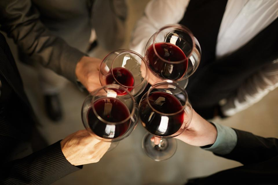 Top view closeup of people in formalwear clinking wine glasses during event, copy space