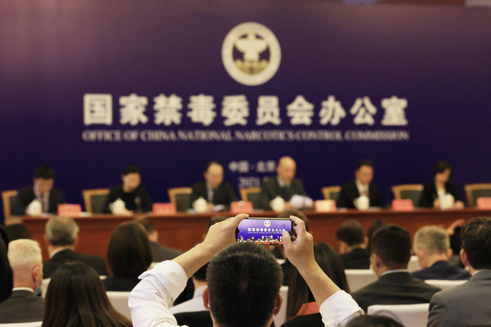 An attendee takes a photo of the press conference held by China's National Narcotics Control Commission in Beijing on Tuesday, May 11, 2021. China on Tuesday said it will add all synthetic cannabinoids to its list of banned drugs, in what it described as a first in the world, to curb their manufacturing, trafficking and abuse. (AP Photo/Ng Han Guan)