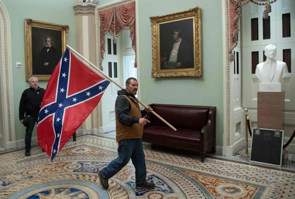 A supporter of Donald Trump carries a Confederate flag inside the US Capitol – next to portraits of John C Calhoun, left, and Charles Sumner, pro- and anti-slavery politicians of the mid-19th century.