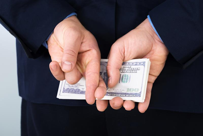A businessman in a suit holding a stack of hundred-dollar bills behind his back with his fingers crossed.
