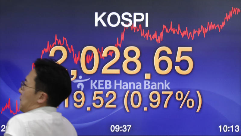 A currency trader walks by the screen showing the Korea Composite Stock Price Index (KOSPI) at the foreign exchange dealing room in Seoul, South Korea, Monday, Sept. 9, 2019. (AP Photo/Lee Jin-man)
