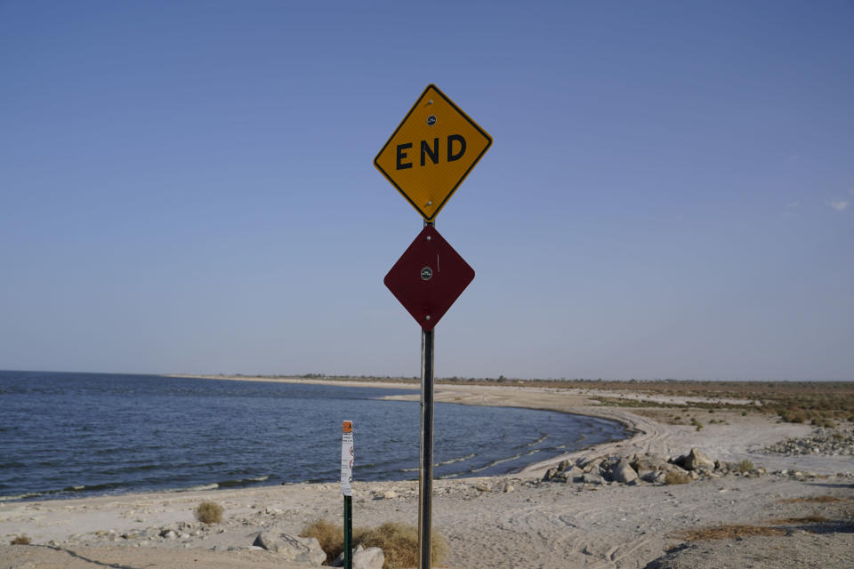 A sign is posted at the end of a road leading to the Salton Sea in Desert Shores, Calif., Wednesday, July 14, 2021. Demand for electric vehicles has shifted investments into high gear to extract lithium from geothermal wastewater around the shrinking body of water. The ultralight metal is critical to rechargeable batteries. (AP Photo/Marcio Jose Sanchez)