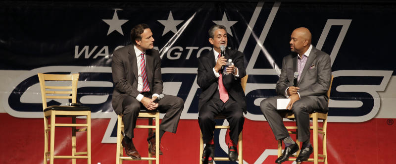 Washington Capitals majority owner Ted Leonsis, center, speaks as NHL Chief Operating Officer John Collins, left, and moderator Michael Wilbon, right, look on during the team's Capitals Convention, Saturday, Sept. 21, 2013, in Washington. Leonsis announced that the team will host the league's annual Winter Classic outdoor hockey game on New Year's Day in 2015. (AP Photo/Luis M. Alvarez)