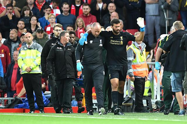 Alisson Becker leaves the pitch following an injury during the Premier League opener. (Photo by Michael Regan/Getty Images)