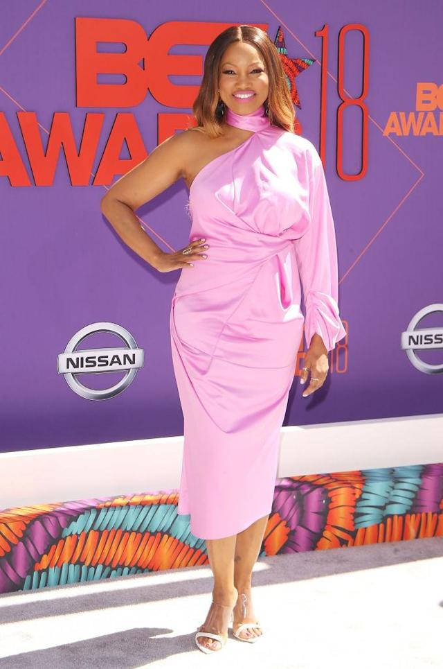 <p>Garcelle Beauvais's soft and sultry ombre 'do is the perfect complement to her pretty-in-pink dress. (Photo: Getty Images) </p>