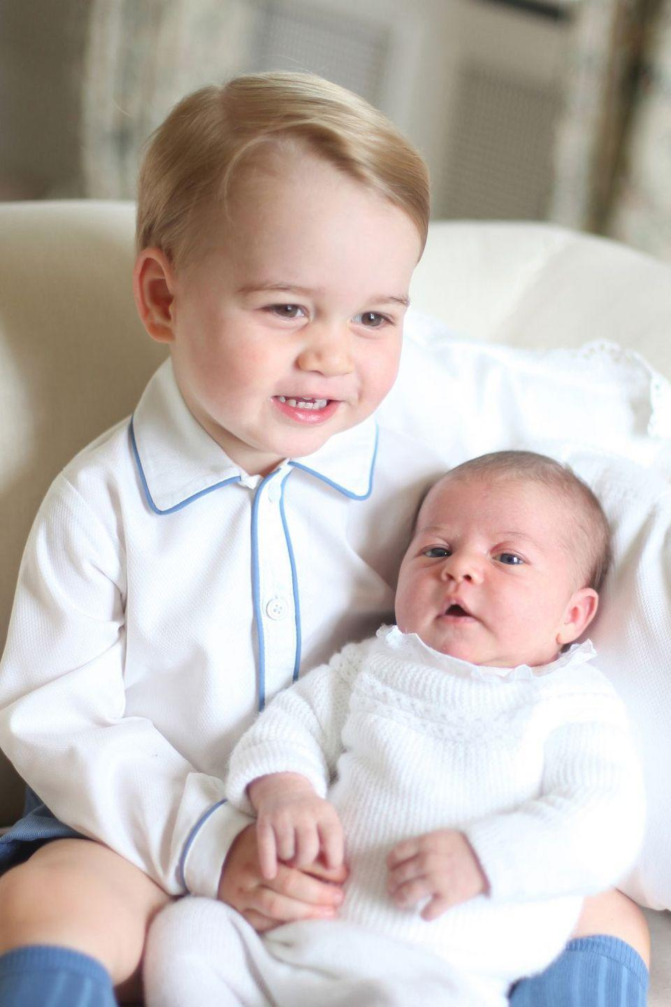 <p>Prince George smiles while holding his newborn sister, Princess Charlotte, who was born on May 2, 2015. Kate Middleton captured the photo when her daughter was less than a month old, at the Duke and Duchess' country home, Anmer Hall, in Norfolk, England. </p>