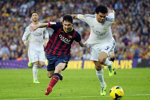Real Madrid's Pepe, right, duels for the ball against FC Barcelona's Lionel Messi during the Spanish La Liga soccer match against FC Barcelona at the Camp Nou stadium in Barcelona, Spain, Saturday, Oct. 26, 2013. (AP Photo/Manu Fernandez)