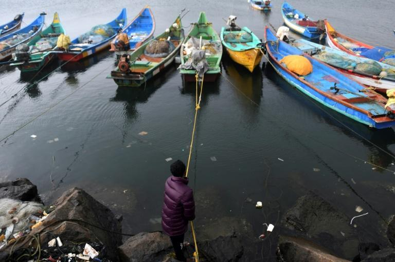 A fisherman anchors his boat at Kasimedu fishing harbour in Chennai as Cyclone Nivar approaches on November 24, 2020
