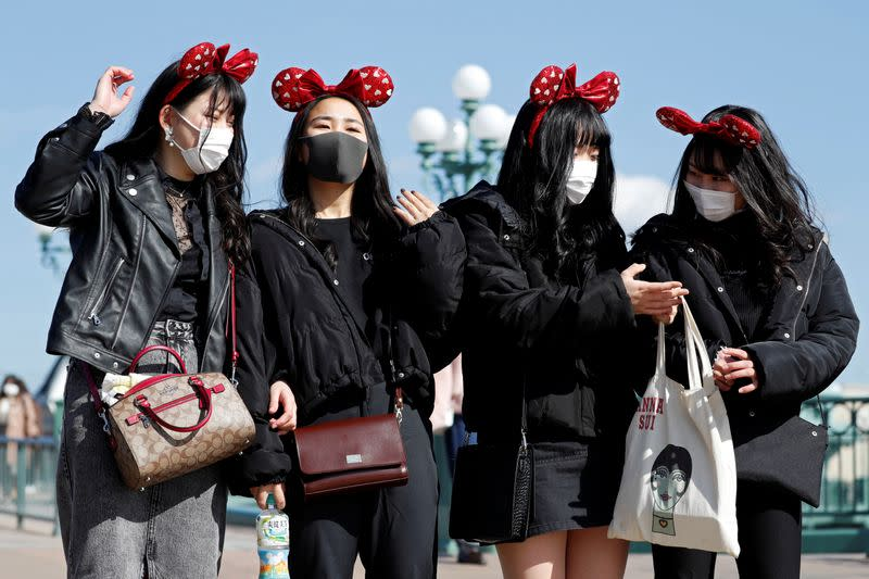 Visitors wearing protective face masks and Minnie Mouse costumes, following an outbreak of the coronavirus, are seen outside Tokyo Disneyland in Urayasu