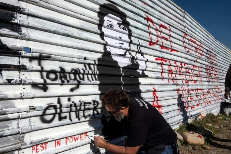 Manuel Oliver, seen on the Mexican side of the border with the US in front of a portrait of his slain son Joaquin