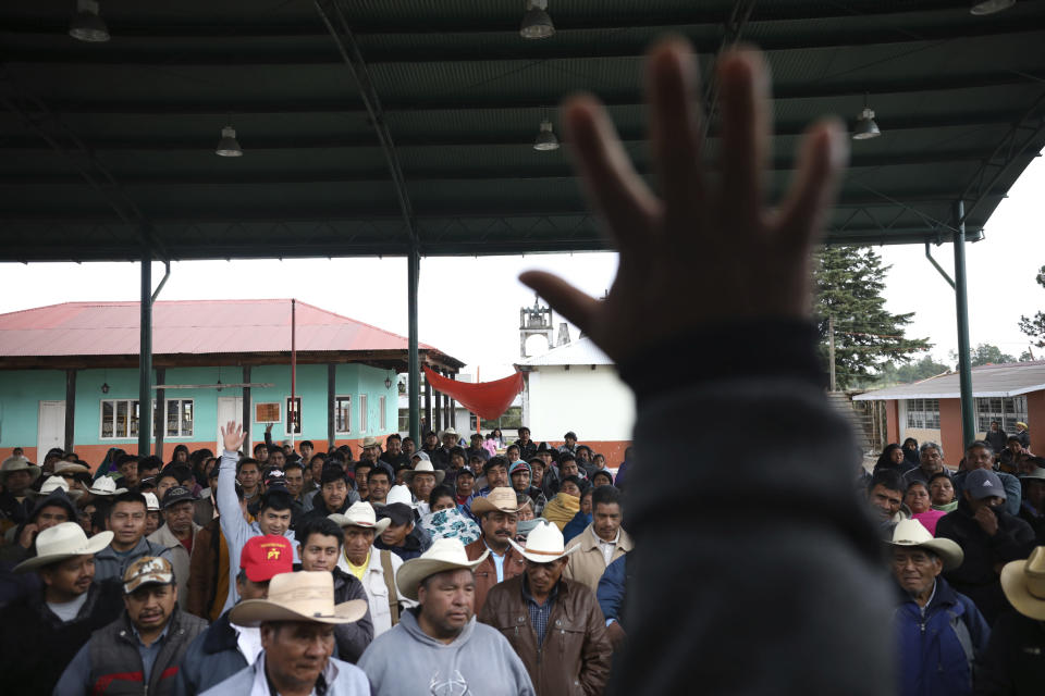 Indigenous Tzotzil men meet during the day of a non-binding national referendum on whether Mexican ex-presidents should be tried for any illegal acts during their time in office, at the Corazon de Maria community, in Chiapas state, Mexico, Sunday, August 1, 2021. (AP Photo/Emilio Espejel)