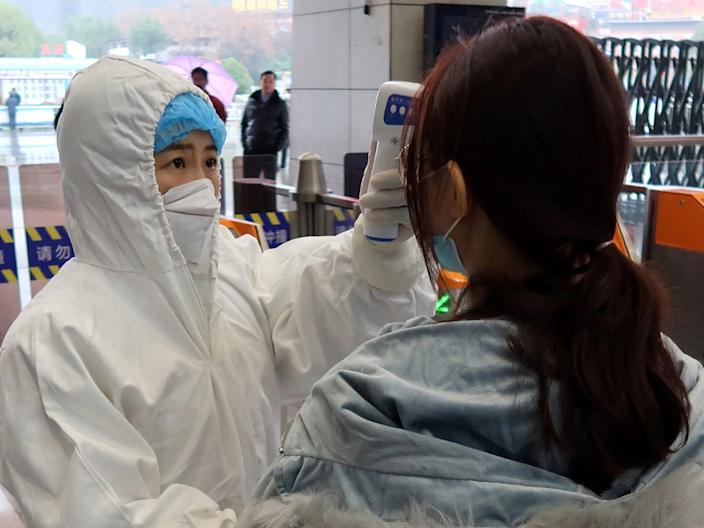 A worker in a protective suit checks the temperature of a passenger who arrives on January 24, 2020 at Xianning North Railway Station in Xianning, a city in the north of Wuhan, Hubei Province, China.