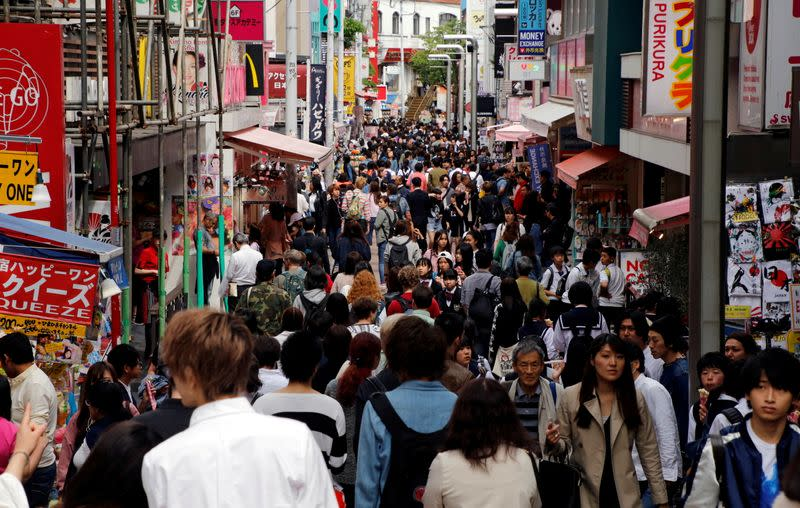 FILE PHOTO: People walk on a street in a busy shopping district in Tokyo