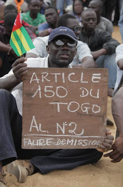 In this Saturday, Aug. 25, 2012 photo, an opposition protestor holds a sign reading 'Faure, Resign,' referring to Togo's president, Faure Gnassingbe, and citing an article of the constitution that protesters say gives them the right to engage in civil disobedience, during an opposition sit-in in Lome, Togo. The female wing of a civil rights group is urging women in Togo to stage a week-long sex strike to demand the resignation of the country's president. Earlier this month, two anti-Gnassingbe protests were dispersed by police using tear gas and more than 100 people were arrested.(AP Photo/ Erick Kaglan)