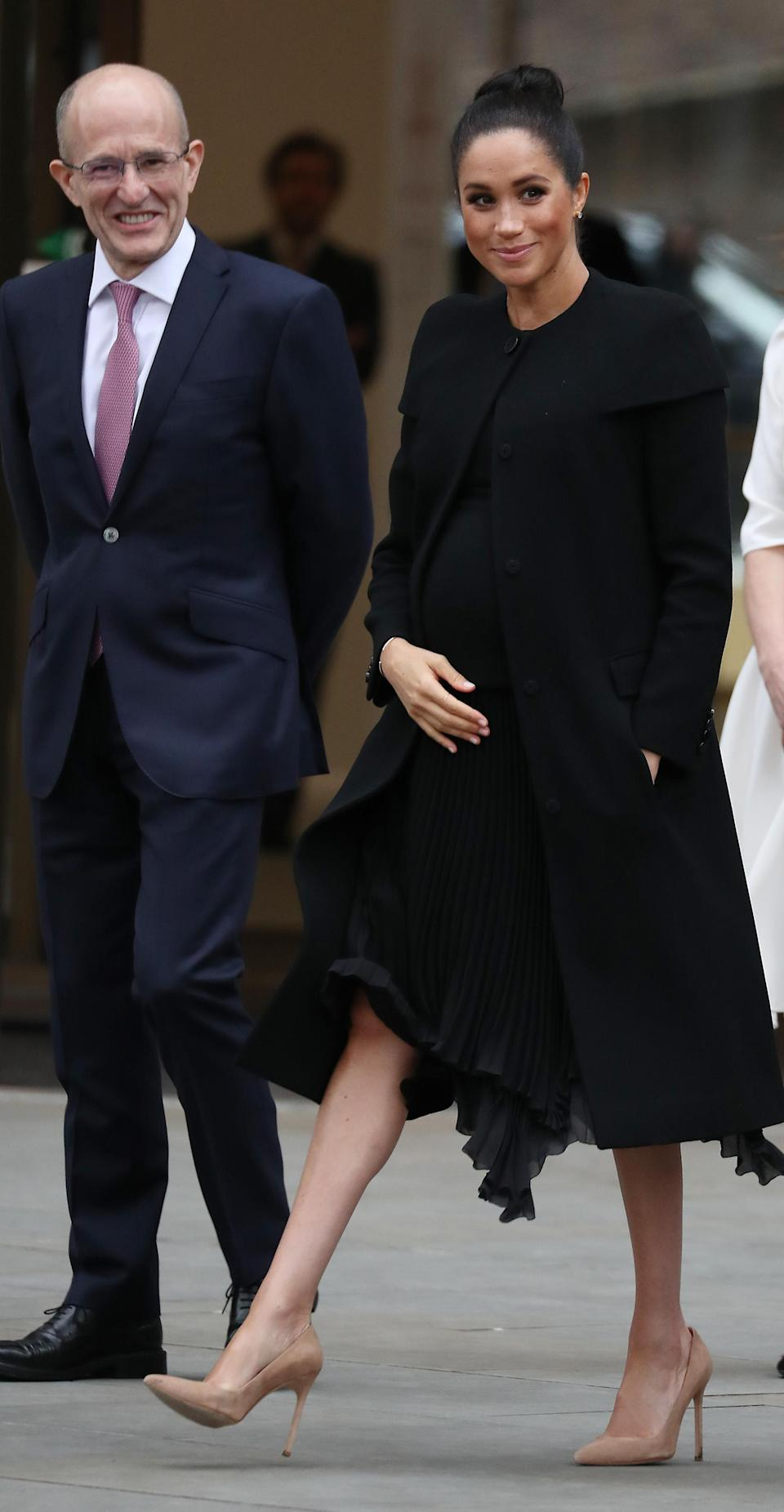 The Duchess of Sussex swapped her trademark messy bun for a slick updo during a trip to the Association of Commonwealth Universities at City, University Of London. She wore a minimal ensemble which included a chic Givenchy coat and matching pleated dress. [Photo: Getty]
