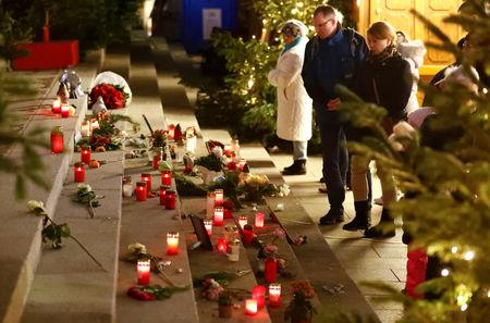 FILE PHOTO: Visitors silently observe in front of a memorial at the site of the Christmas market's truck attack, which killed 12 people and injured many others two years ago on December 19, at Breitscheidplatz square in Berlin, Germany, December 17, 2018. REUTERS/Fabrizio Bensch/File Photo