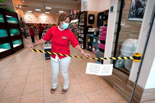 PHOTO: Store manager Natalie Hijazi temporarily closes off the entrance to store inside The Woodlands Mall to help meet occupancy limits, May 5, 2020, in The Woodlands, Texas. (David J. Phillip/AP)