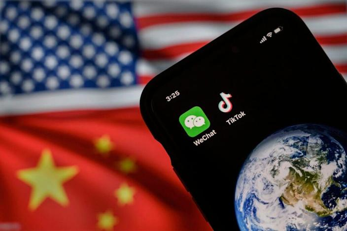 In this photo illustration, a mobile phone can be seen displaying the logos for Chinese apps WeChat and TikTok in front of a monitor showing the flags of the United States and China on an internet page, on September 22, 2020 in Beijing, China. (Photo by Kevin Frayer/Getty Images)