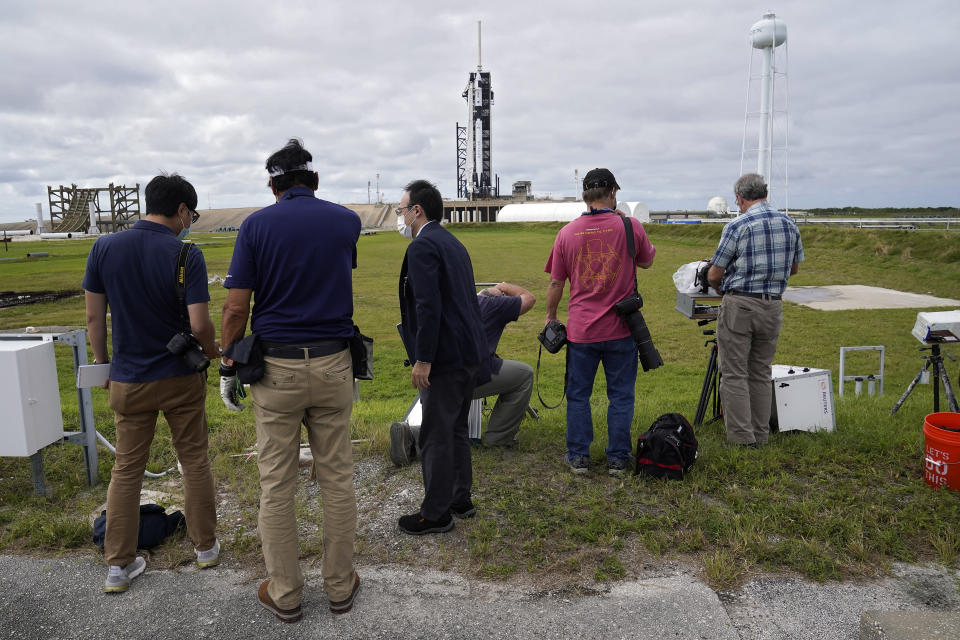 Photographers set up remote cameras near a SpaceX Falcon 9 rocket, with the company's Crew Dragon capsule attached, as she sits on the launch pad at Launch Complex 39A Friday, Nov. 13, 2020, at the Kennedy Space Center in Cape Canaveral, Fla. Four astronauts will fly on the SpaceX Crew-1 mission to the International Space Station scheduled for launch on Nov. 14, 2020 (AP Photo/Chris O'Meara)