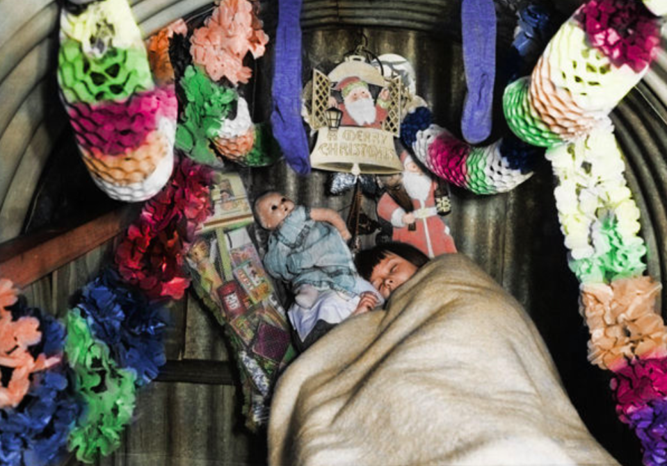 <p>A child sleeps cuddles up with her doll in an Anderson air raid shelter full of Christmas decorations. (MediaDrumWorld) </p>