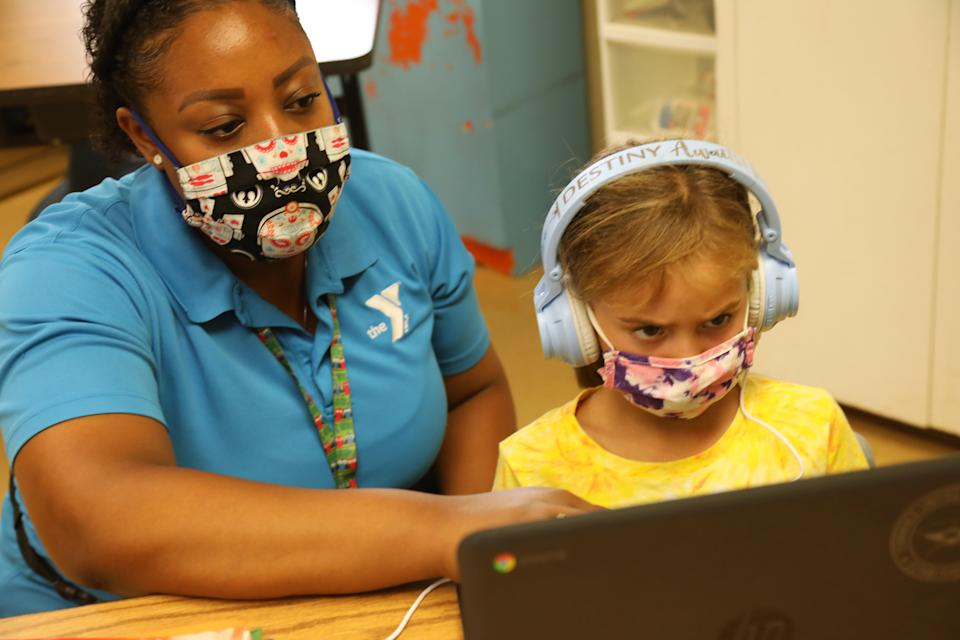 TORRANCE, CA - SEPTEMBER 17, 2020 - - Denecia Boone, left, a teacher with the YMCA, helps Maya Haldeman with an exercise at the Anza Elementary School campus in Torrance on September 17, 2020. Anza Elementary School is one of many schools that are reformatting and rebranding as camps, enrichment programs and daycare, bringing students back to closed campuses for a fee. Torrance Unified School District is one of many that now offers fee-based, in person enrichment for its elementary school students, through the YMCA. (Genaro Molina / Los Angeles Times via Getty Images)