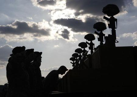 U.S. soldiers pay their respects in front of fallen soldier memorials for the shooting victims after the III Corps and Fort Hood Memorial Ceremony at Fort Hood, Texas, November 10, 2009 in this file photo.  REUTERS/Jessica Rinaldi