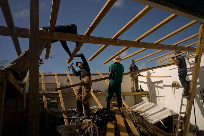 <p>Workers repair research facilities destroyed by Hurricane Maria in Cayo Santiago, known as Monkey Island, in Puerto Rico on Oct. 4, 2017. Mainland scientists are bringing in equipment from chain saws to a portable pier, funded by tens of thousands of dollars raised so far in university departments and online. (Photo: Ramon Espinosa/AP) </p>
