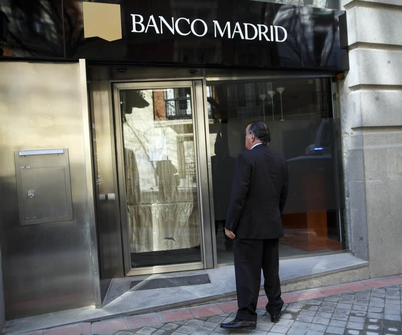 Man stands in front of the entrance of a closed Banco Madrid branch in Madrid