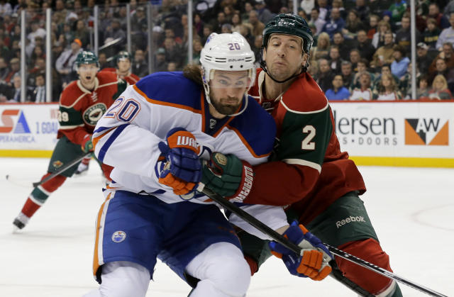 Minnesota Wild defenseman Keith Ballard (2) holds Edmonton Oilers left wing Luke Gazdic (20) off the puck during the second period of an NHL hockey game in St. Paul, Minn., Tuesday, March 11, 2014. (AP Photo/Ann Heisenfelt)