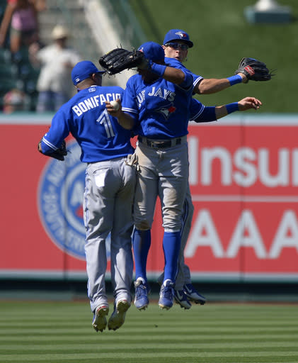 Toronto Blue Jays' Emilio Bonifacio, left, Rajai Davis, center, and Colby Rasmus celebrate after defeating the Los Angeles Angels in their baseball game, Sunday, Aug. 4, 2013, in Anaheim, Calif. (AP Photo/Mark J. Terrill)