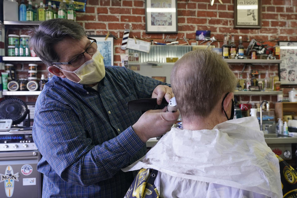 FILE — In this Thursday Jan. 21, 2021 file photo Mike Douglass, left, gives Kent Kjestrom a haircut at East J Barbers in Sacramento, Calif. California Health and Human Services Secretary Dr. Mark Ghaly explained the math behind the state's calculation of when it is safe to lift it's stay-at-home order and overnight curfew, during a news briefing Tuesday, Jan. 26, 2021. (AP Photo/Rich Pedroncelli, File)