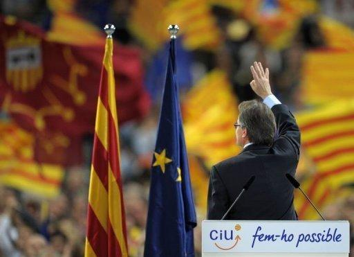 Artur Mas waves at supporters at the end of a final meeting for his re-election campaign