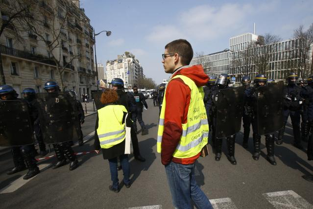 Yellow vest protesters are blocked by police in Paris, Saturday, March 23, 2019. The French government vowed to strengthen security as yellow vest protesters stage a 19th round of demonstrations, in an effort to avoid a repeat of last week's riots in Paris. (AP Photo/Michel Euler)
