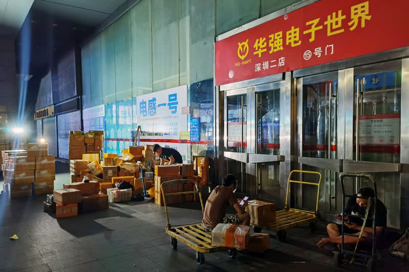 Delivery men take a break outside a closed electronics market in Shenzhen's Huaqiangbei area