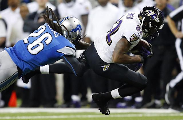 Baltimore Ravens wide receiver Torrey Smith (82) is stopped by Detroit Lions free safety Louis Delmas (26) during the second quarter of an NFL football game in Detroit, Monday, Dec. 16, 2013. (AP Photo/Rick Osentoski)