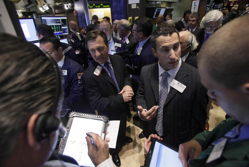 FILE - In a Thursday, July 26, 2012 photo, traders gather at a post on the floor of the New York Stock Exchange during the IPO of Northern Tier Energy. U.S. stocks crept higher in early  trading Monday, July 30, 2012 on Wall Street following big gains last week. (AP Photo/Richard Drew, File)
