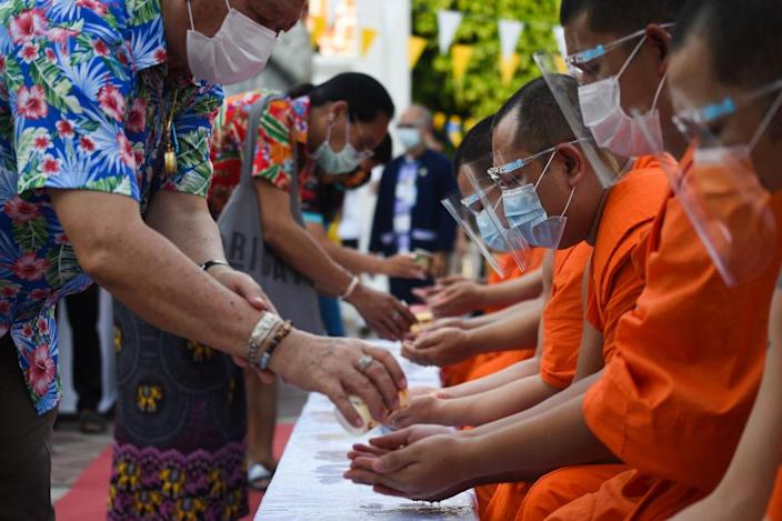 """People queue to pour water on a Buddhist statue as they celebrate Songkran, also known as the Thai New Year, at Wat Pho temple in Bangkok, Thailand on 13 April 2021.<span class=""""copyright"""">Anusak Laowilas—NurPhoto/Getty Images</span>"""