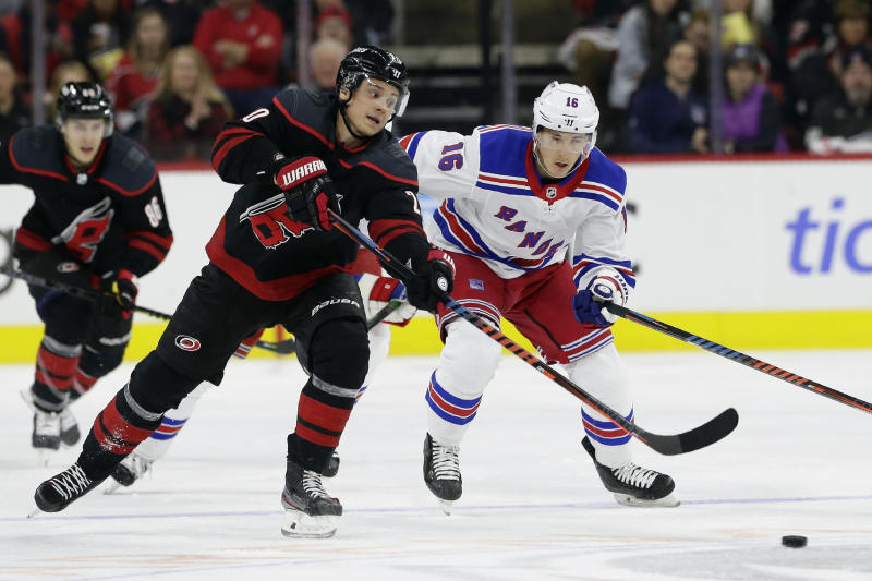 Carolina Hurricanes center Sebastian Aho, left, of Finland, skates for the puck against New York Rangers center Ryan Strome (16) during the second period of an NHL hockey game in Raleigh, N.C., Friday, Feb. 21, 2020. (AP Photo/Gerry Broome)