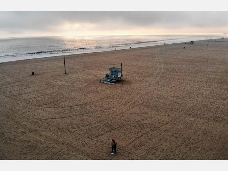 VENICE, CALIFORNIA - APRIL 26: An aerial view of people embracing before sunset on a nearly empty Venice Beach, which remains closed along with all other Los Angeles County beaches under stay-at-home orders, amid the coronavirus pandemic on April 26, 2020